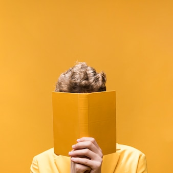 Junger gutaussehender mann, der ein buch in einer gelben szene liest