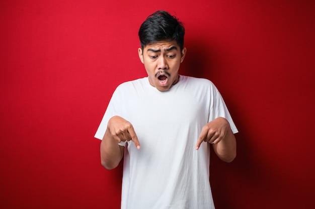Junger gutaussehender mann, der ein lässiges hemd trägt, das auf rotem hintergrund steht und mit den fingern nach unten zeigt, die werbung, überraschtes gesicht und offenen mund zeigen