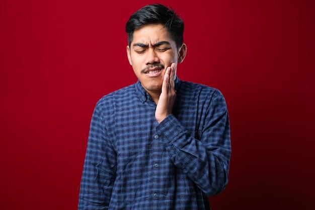 Junger gutaussehender mann, der ein lässiges hemd trägt, das über isoliertem rotem hintergrund steht und den mund mit der hand mit schmerzhaftem ausdruck wegen zahnschmerzen oder zahnerkrankungen an den zähnen berührt zahnarzt
