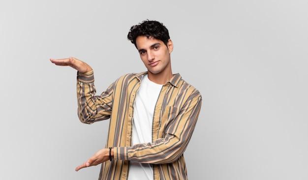 Junger gutaussehender mann, der ein objekt mit beiden händen auf seitenkopierraum hält und ein objekt zeigt, anbietet oder wirbt