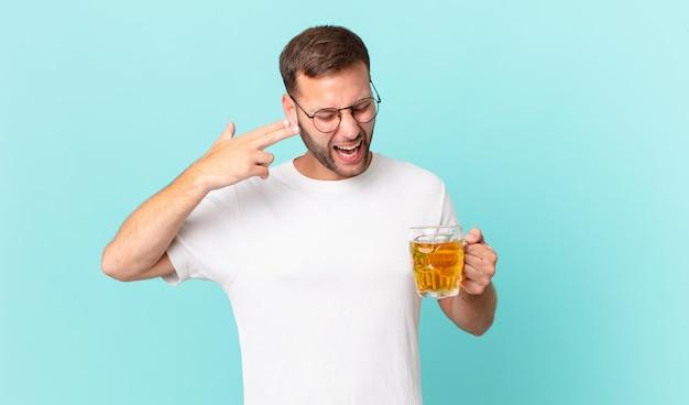 Junger gutaussehender mann, der ein pint bier trinkt