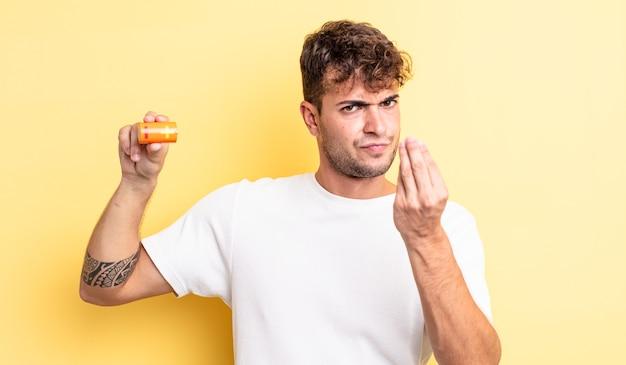 Junger gutaussehender mann, der eine capice- oder geldgeste macht und ihnen sagt, dass sie mit einer batterie bezahlen sollen