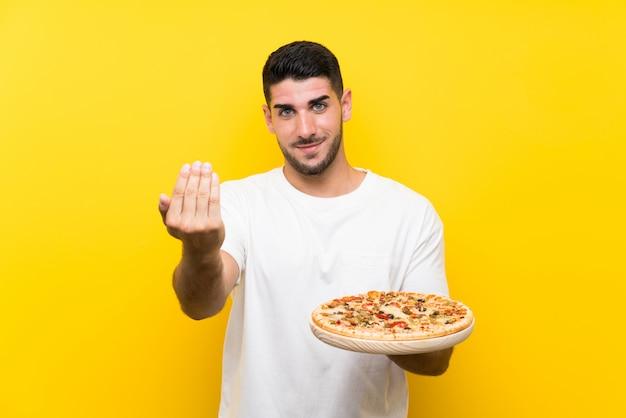 Junger gutaussehender mann, der eine pizza über der lokalisierten gelben wand einlädt, mit der hand zu kommen hält