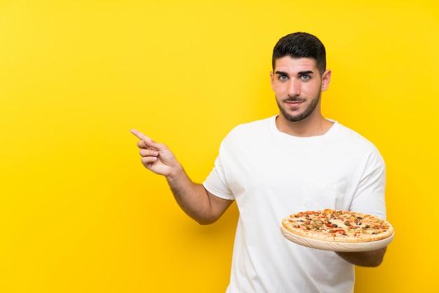 Junger gutaussehender mann, der eine pizza über der lokalisierten gelben wand zeigt auf die seite hält, um ein produkt darzustellen