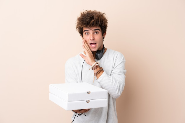 Junger gutaussehender mann, der eine pizza über der lokalisierten wand flüstert etwas hält