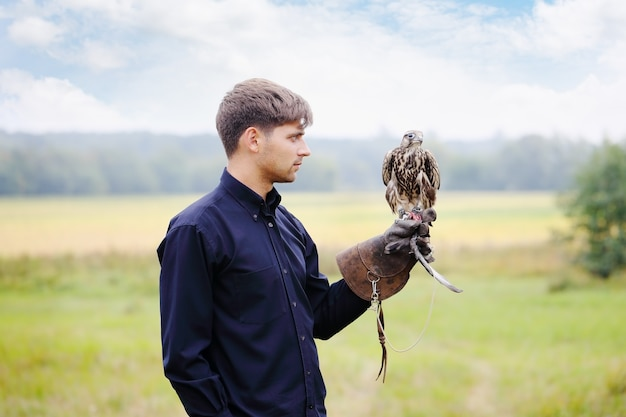 Junger gutaussehender mann, der einen falken auf seinem arm hält