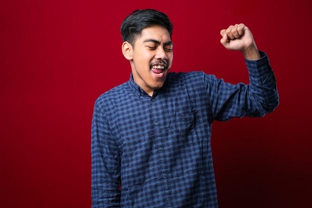 Junger gutaussehender mann, der einen lässigen pullover trägt, der über isoliertem rotem hintergrund steht, sehr glücklich und aufgeregt, der die gewinnergeste mit erhobenen armen macht, lächelt und nach erfolg schreit. feierkonzept