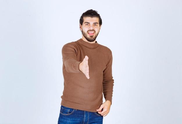 Junger gutaussehender mann, der einen lässigen pullover über isoliertem weißem hintergrund trägt, lächelt fröhlich und bietet palmenhand an, die hilfe und akzeptanz gibt. foto in hoher qualität