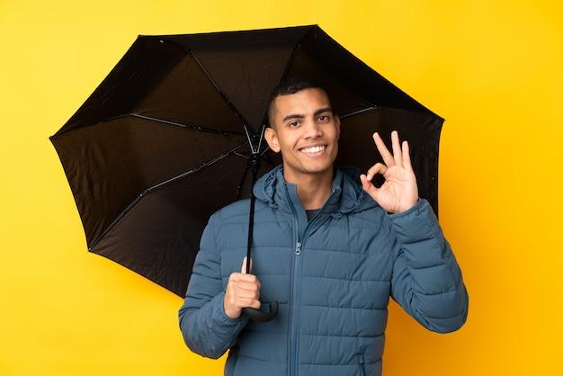 Junger gutaussehender mann, der einen regenschirm über der lokalisierten gelben wand zeigt okayzeichen mit den fingern hält