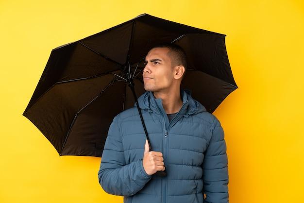 Junger gutaussehender mann, der einen regenschirm über lokalisierter gelber wand mit traurigem ausdruck hält
