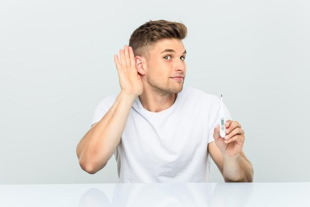 Junger gutaussehender mann, der einen thermometer versucht, einen klatsch zu hören hält.