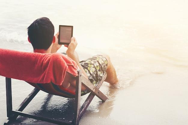 Junger gutaussehender mann, der elektronischen leser am strand liest