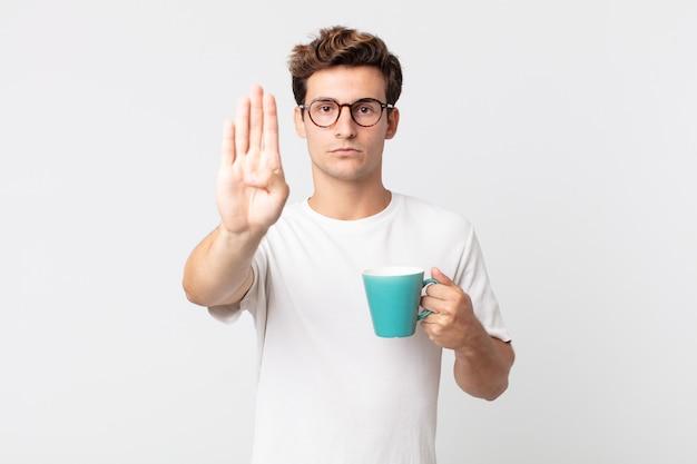 Junger gutaussehender mann, der ernst aussieht und eine offene handfläche zeigt, die stopp-geste macht und eine kaffeetasse hält