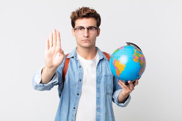 Junger gutaussehender mann, der ernst aussieht und offene handfläche zeigt, die stopp-geste macht. student, der eine weltkugelkarte hält