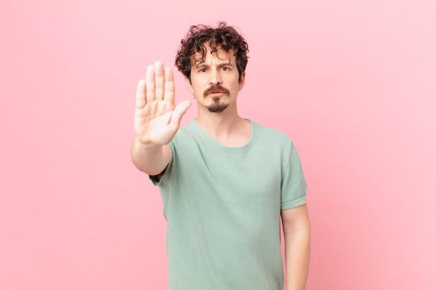 Junger gutaussehender mann, der ernst aussieht und offene handfläche zeigt, die stopp-geste macht