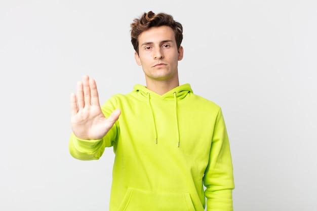 Junger gutaussehender mann, der ernst, streng, unzufrieden und wütend aussieht und eine offene handfläche zeigt, die eine stopp-geste macht