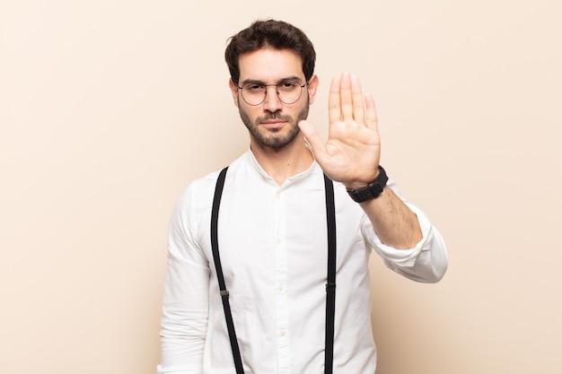 Junger gutaussehender mann, der ernst, streng, unzufrieden und wütend aussieht und offene handfläche zeigt, die stoppgeste macht