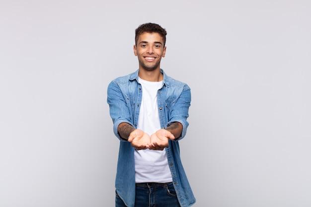 Junger gutaussehender mann, der etwas mit seinen händen anbietet