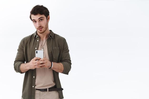 Junger gutaussehender mann, der foto macht und smartphone hält holding