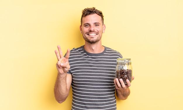 Junger gutaussehender mann, der freundlich lächelt und aussieht und das konzept der kaffeebohnen nummer drei zeigt