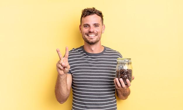 Junger gutaussehender mann, der freundlich lächelt und aussieht und das konzept der kaffeebohnen nummer zwei zeigt