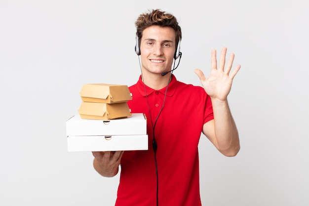 Junger gutaussehender mann, der freundlich lächelt und aussieht und nummer fünf zeigt. take-away-fast-food-konzept