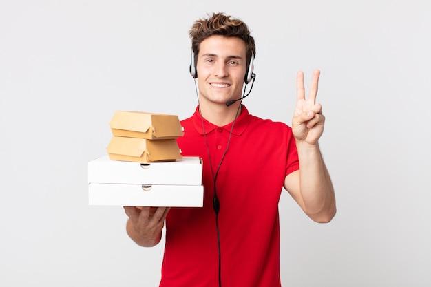 Junger gutaussehender mann, der freundlich lächelt und aussieht und nummer zwei zeigt. take-away-fast-food-konzept