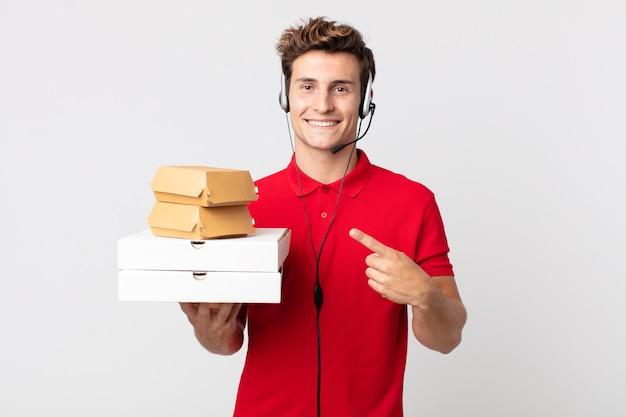 Junger gutaussehender mann, der fröhlich lächelt, sich glücklich fühlt und auf die seite zeigt. take-away-fast-food-konzept