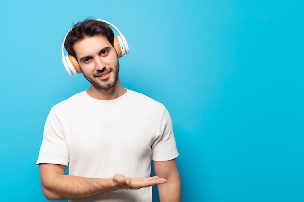 Junger gutaussehender mann, der fröhlich lächelt, sich glücklich fühlt und ein konzept im kopienraum mit handfläche zeigt