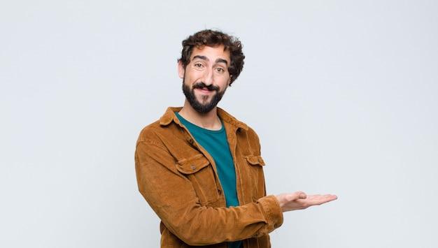 Junger gutaussehender mann, der fröhlich lächelt, sich glücklich fühlt und ein konzept im kopierraum mit handfläche gegen flache wand zeigt
