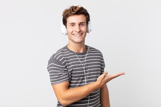 Junger gutaussehender mann, der fröhlich lächelt, sich glücklich fühlt und ein konzept zeigt. musikkonzept hören
