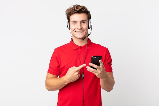 Junger gutaussehender mann, der fröhlich lächelt, sich glücklich fühlt und mit einem smartphone und headset auf die seite zeigt