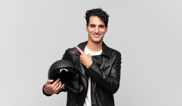 Junger gutaussehender mann, der fröhlich lächelt, sich glücklich fühlt und zur seite und nach oben zeigt und objekt im kopierraum zeigt. motorradfahrerkonzept