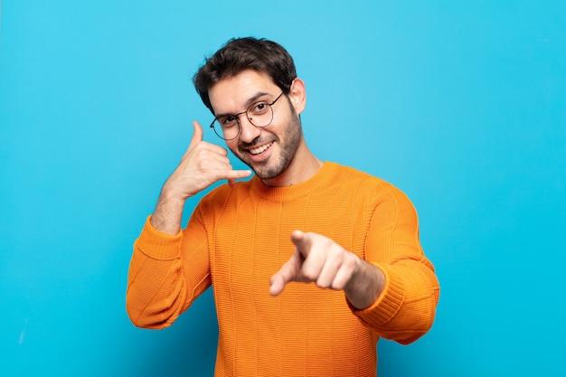 Junger gutaussehender mann, der fröhlich lächelt und auf kamera zeigt, während sie einen anruf tätigen, den sie später gestikulieren und am telefon sprechen