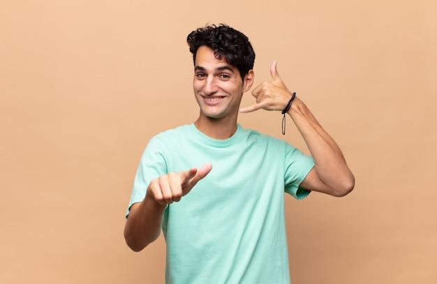 Junger gutaussehender mann, der fröhlich lächelt und zur kamera zeigt, während sie einen anruf tätigen, den sie später gestikulieren und am telefon sprechen