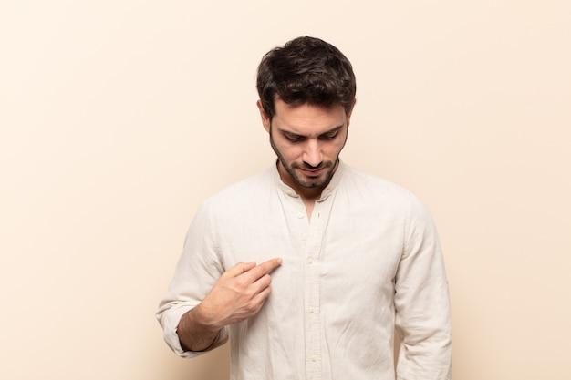 Junger gutaussehender mann, der fröhlich und beiläufig lächelt, nach unten schaut und auf die brust zeigt