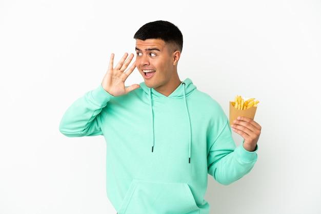 Junger gutaussehender mann, der gebratene chips über isoliertem weißem hintergrund hält und etwas hört, indem er die hand auf das ohr legt
