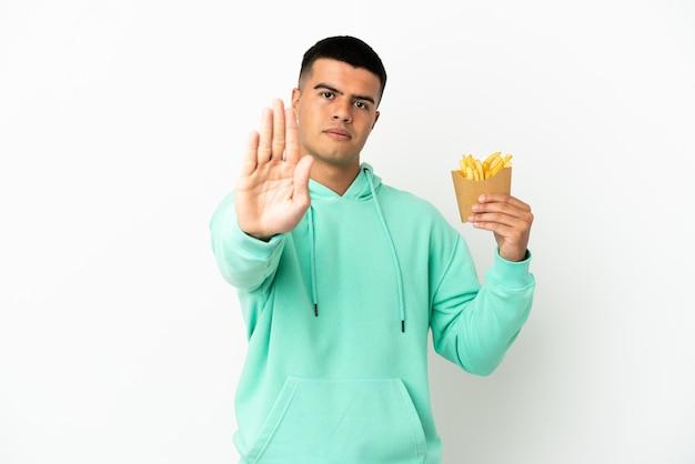 Junger gutaussehender mann, der gebratene chips über isoliertem weißem hintergrund hält und stopp-geste macht