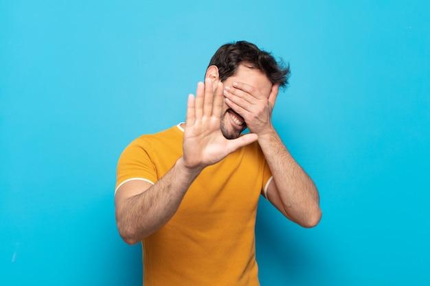 Junger gutaussehender mann, der gesicht mit hand bedeckt und andere hand nach vorne legt, um kamera zu stoppen, fotos oder bilder ablehnend
