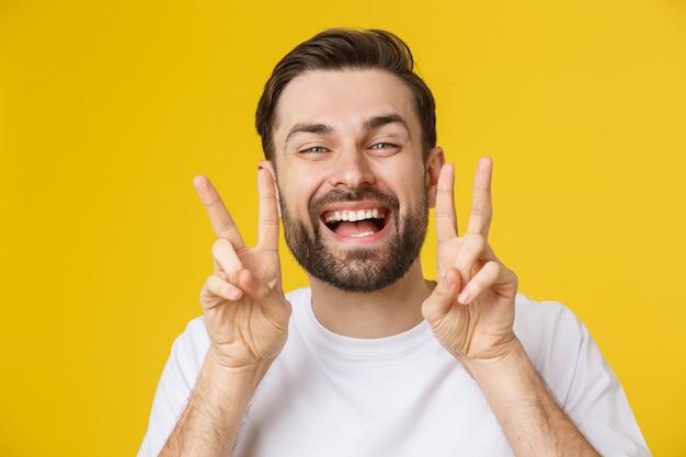 Junger gutaussehender mann, der gestreiftes t-shirt über lokalisiertem gelbem lächelndem schauen zur kamera zeigt die finger tut siegeszeichen trägt. nummer zwei