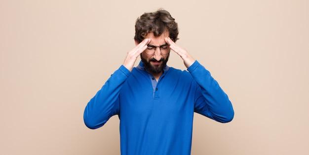 Junger gutaussehender mann, der gestresst und frustriert aussieht, unter druck mit kopfschmerzen arbeitet und mit problemen über der mauer beunruhigt ist