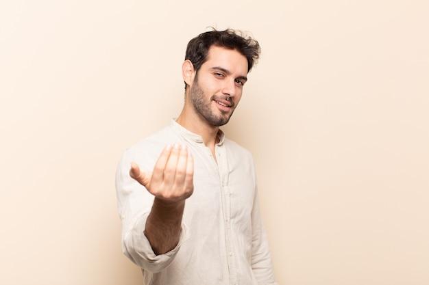 Junger gutaussehender mann, der glücklich, erfolgreich und zuversichtlich fühlt, sich einer herausforderung stellt und sagt, bringen sie es auf! oder dich begrüßen