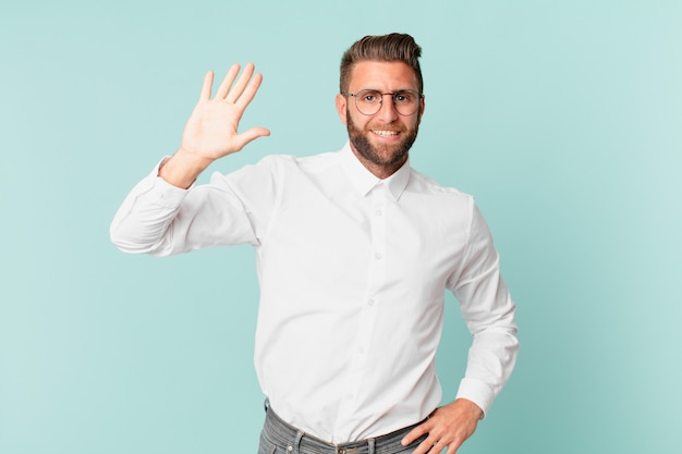 Junger gutaussehender mann, der glücklich lächelt, die hand winkt, sie begrüßt und begrüßt