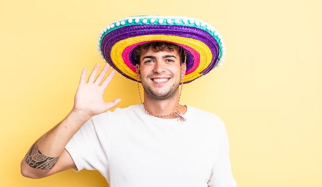 Junger gutaussehender mann, der glücklich lächelt, hand winkt, sie begrüßt und begrüßt. mexikanisches hutkonzept