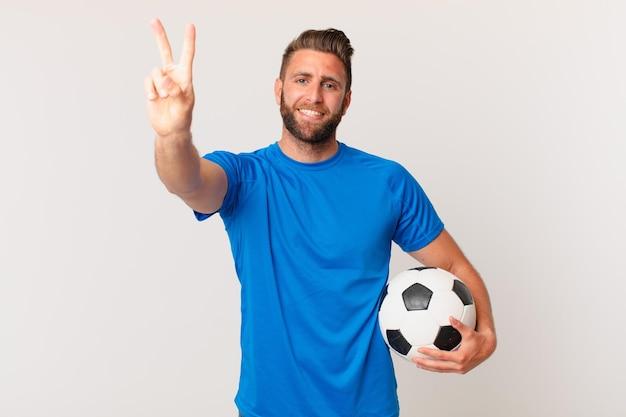 Junger gutaussehender mann, der glücklich lächelt und aussieht und sieg oder frieden gestikuliert. fußballkonzept