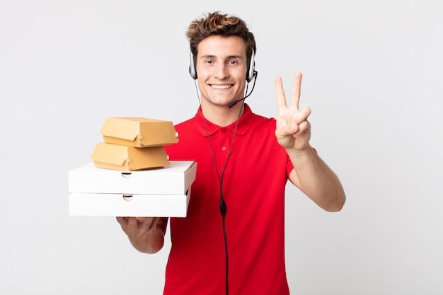 Junger gutaussehender mann, der glücklich lächelt und aussieht und sieg oder frieden gestikuliert. take-away-fast-food-konzept