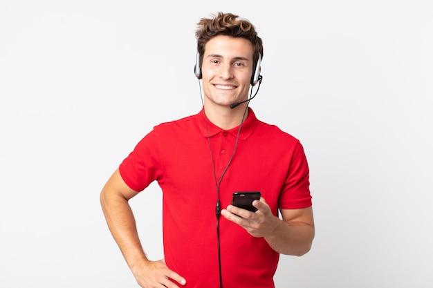 Junger gutaussehender mann, der glücklich mit einer hand auf der hüfte lächelt und mit einem smartphone und einem headset selbstbewusst ist