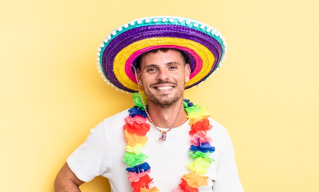 Junger, gutaussehender mann, der glücklich mit einer hand auf der hüfte lächelt und selbstbewusst ist. mexikanisches partykonzept