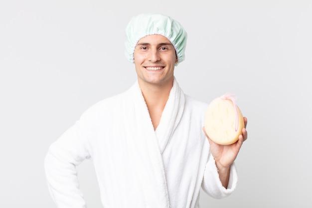 Junger gutaussehender mann, der glücklich mit einer hand auf der hüfte lächelt und selbstbewusst mit bademantel, duschhaube und schwamm