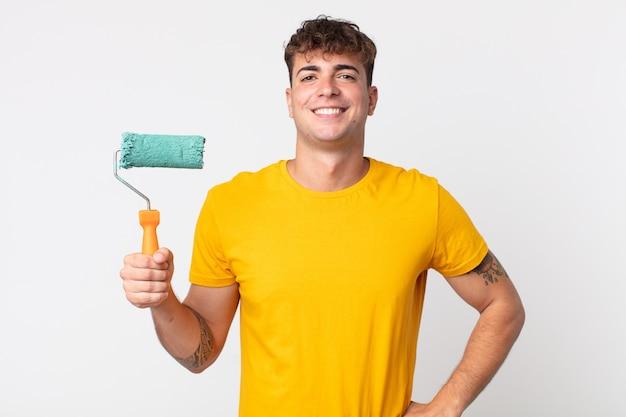 Junger gutaussehender mann, der glücklich mit einer hand auf der hüfte und selbstbewusst lächelt. malerei nach hause konzept